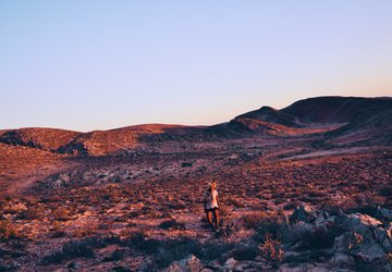An archaeologist walking in the Namaqualand Hills at sunset