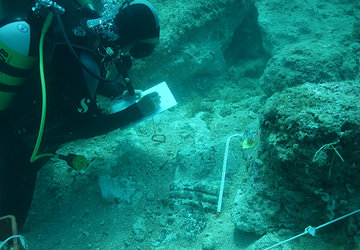 scuba diving student taking measurements during underwater excavation